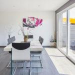 Un espace repas spacieux et lumineux près de la baie vitrée avec accès direct à la terrasse